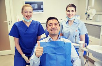 Happy patient with a dentist with thumbs up
